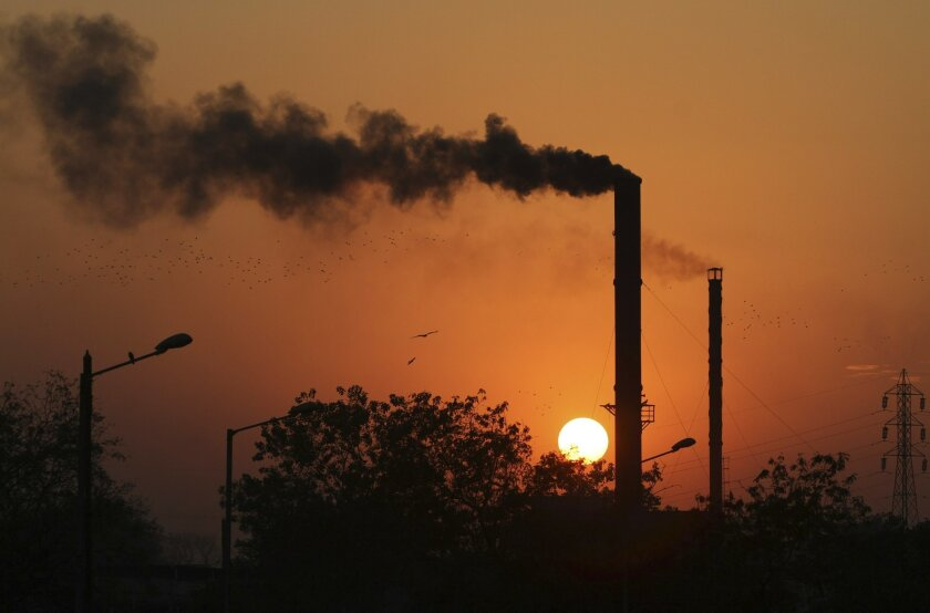 This is a Monday, Dec. 8, 2014 file photo of birds as they fly past at sunset as smoke emits from a chimney at a factory in Ahmadabad, India.