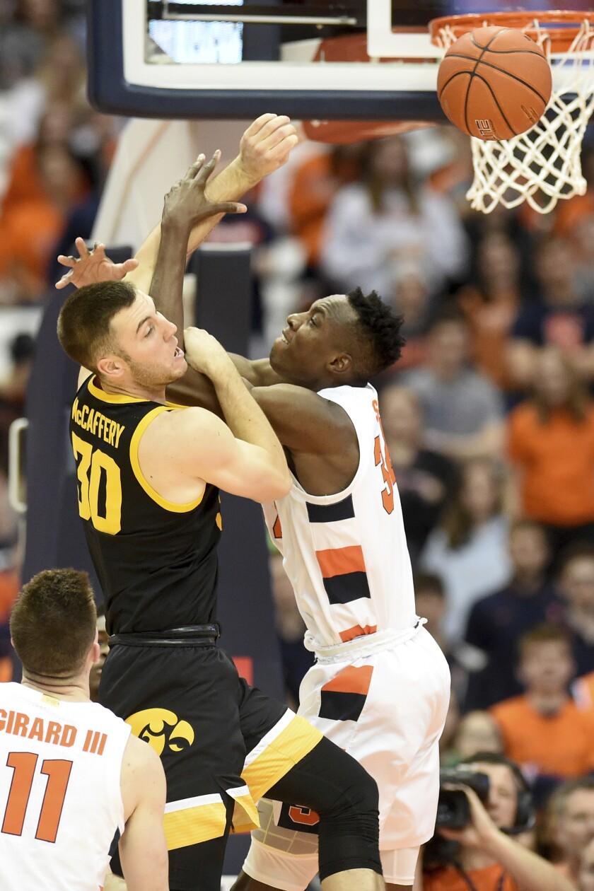 Iowa guard Connor McCaffery (30) and Syracuse center Bourama Sidibe (34) vie for a reboundd uring an NCAA college basketball game Tuesday, Dec. 3, 2019, in Syracuse, N.Y. (Dennis Nett/The Post-Standard via AP)
