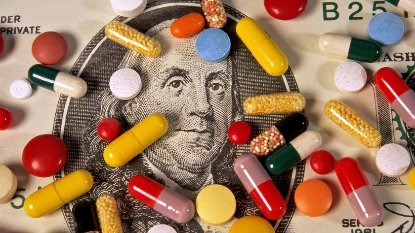 An assortment of pills sits on top of a $100 bill around the portrait of Benjamin Franklin
