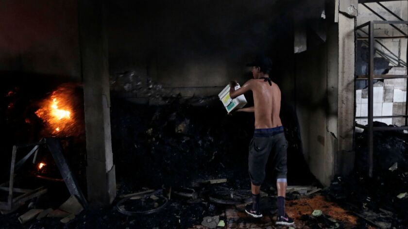 A man works to extinguish what remains of an arson house fire that killed four adults and two children in Managua on Saturday.
