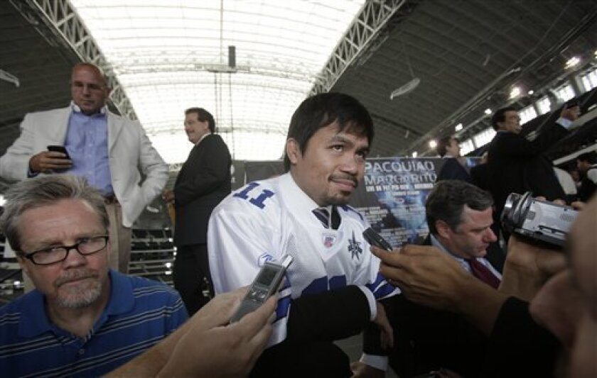 Boxer Manny Pacquiao, center, of the Philippines listens to a question after a pre-fight news conference promoting his upcoming bout at Cowboys Stadium in Arlington, Texas, Friday, Sept. 3, 2010. Pacquiao faces Antonio Margarito, of Mexico, Nov. 13, for the WBC junior middleweight title. AP Photo/LM Otero)