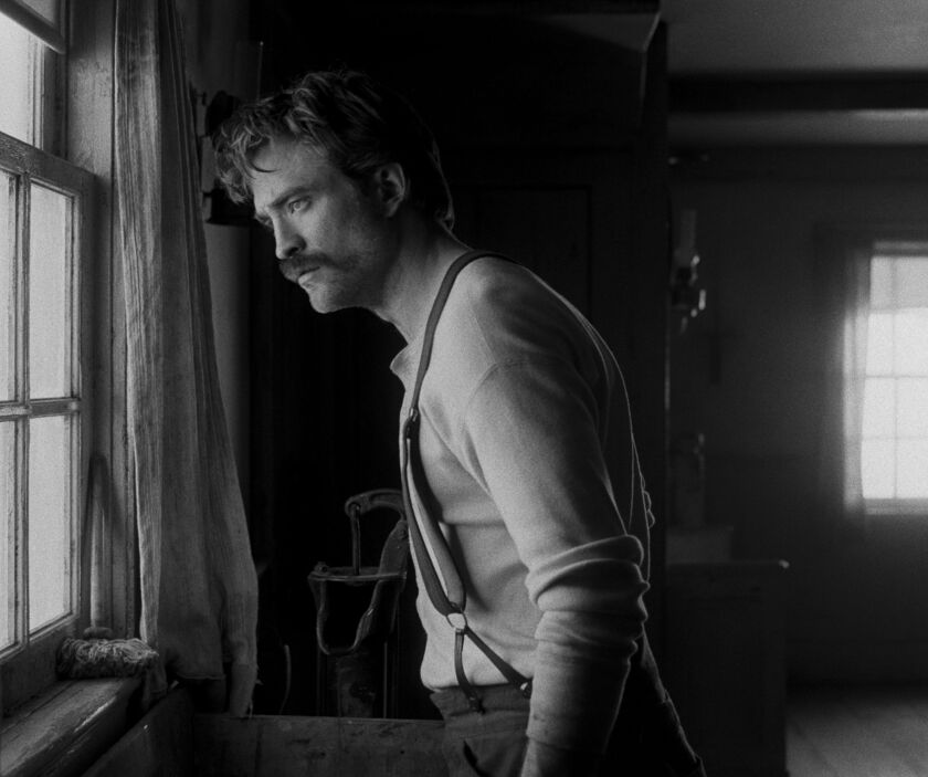 "A mustachioed Robert Pattinson, in suspenders, looks out a window in ""The Lighthouse."""