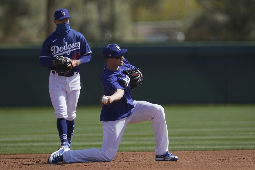 Dodgers shortstop Corey Seager throws to second base as Dodgers infielder Omar Estevez looks on.