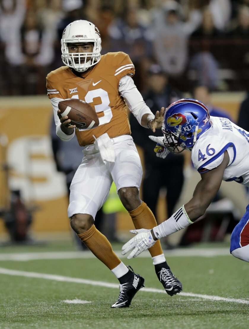 Texas quarterback Jerrod Heard (13) is pressured by Kansas defensive end Dorance Armstrong Jr. (46) during the first half of an NCAA college football game, Saturday, Nov. 7, 2015, in Austin, Texas. (AP Photo/Eric Gay)