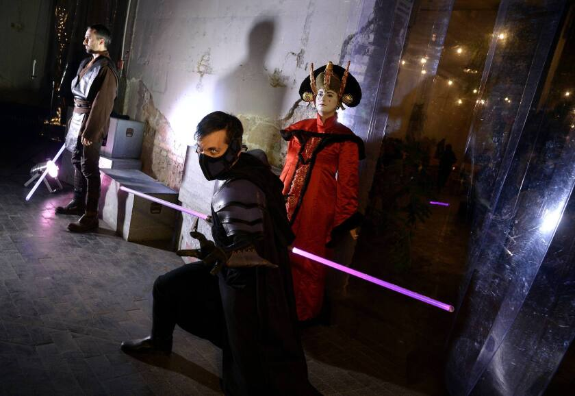 """Party-goers wear """"Star Wars"""" movie character outfits during a party in downtown Rome on the eve of the premiere of """"The Force Awakens."""""""