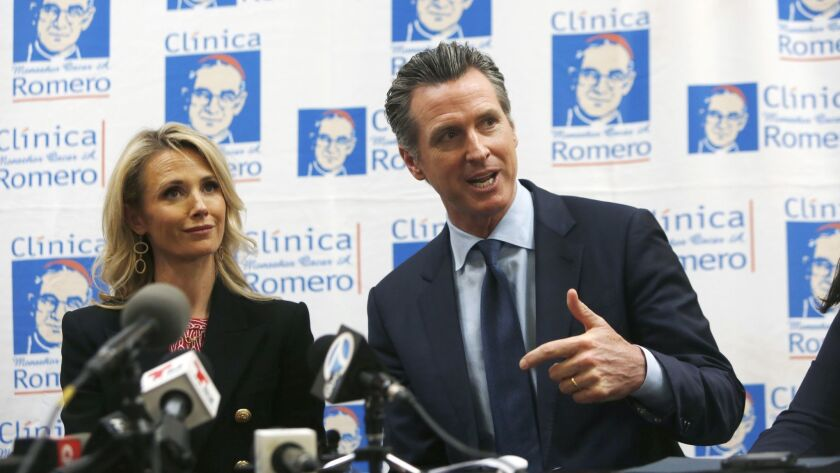 LOS ANGELES, CA-MARCH 28, 2019: Governor Gavin Newsom speaks with wife, Jennifer Siebel, left, durin