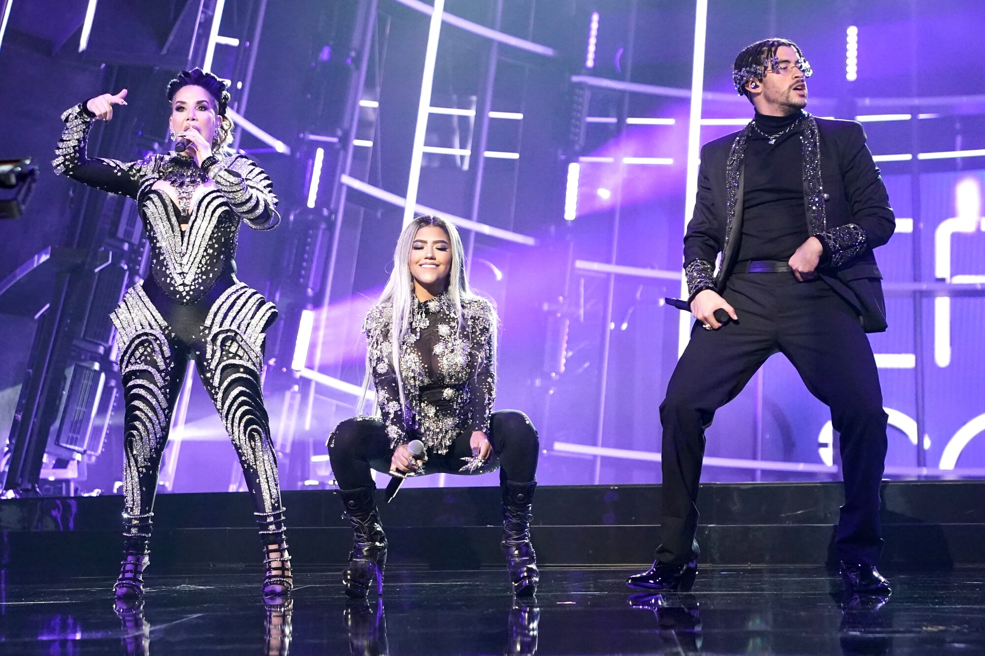 Ivy Queen, Nesi, Bad Bunny perform on a brightly lighted stage.