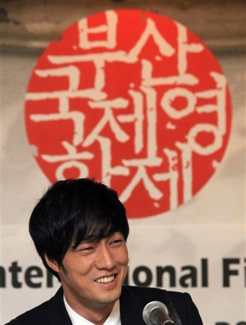 """South Korean actor So Ji-sub of the Busan International Film Festival opening movie """"Always"""" smiles during a press conference in Seoul, South Korea, Thursday, Sept. 8, 2011. The biggest film festival in Asia showcases more than 300 films from 70 and runs from Oct. 6 to Oct. 14. The letters read: """"Busan International Film Festival."""" (AP Photo/Ahn Young-joon)"""