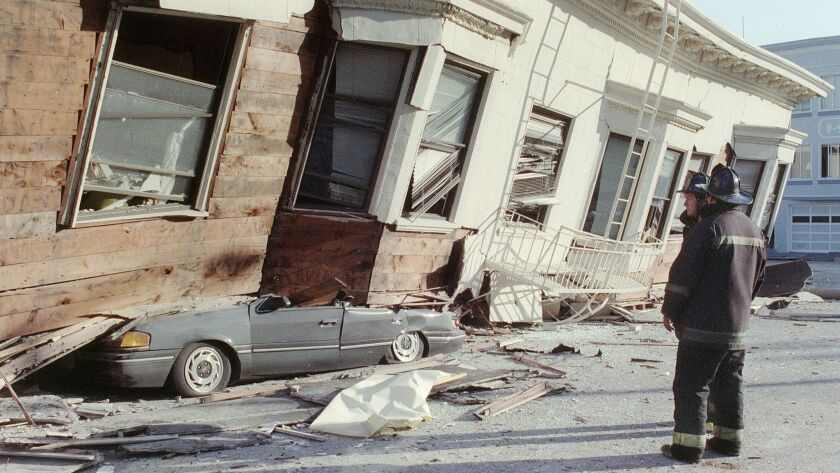 In one of the hardest-hit areas in the 1989 Loma Prieta earthquake, two firemen look at a collapsed building that crushed a car in San Francisco's Marina District.