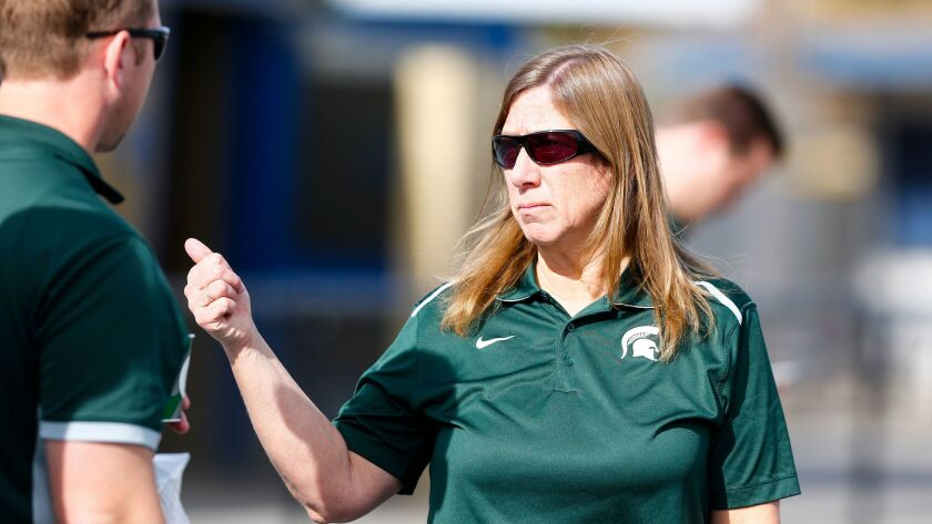 Michigan State trainer Sally Nogle talks with team staff during practice at Mesa College.