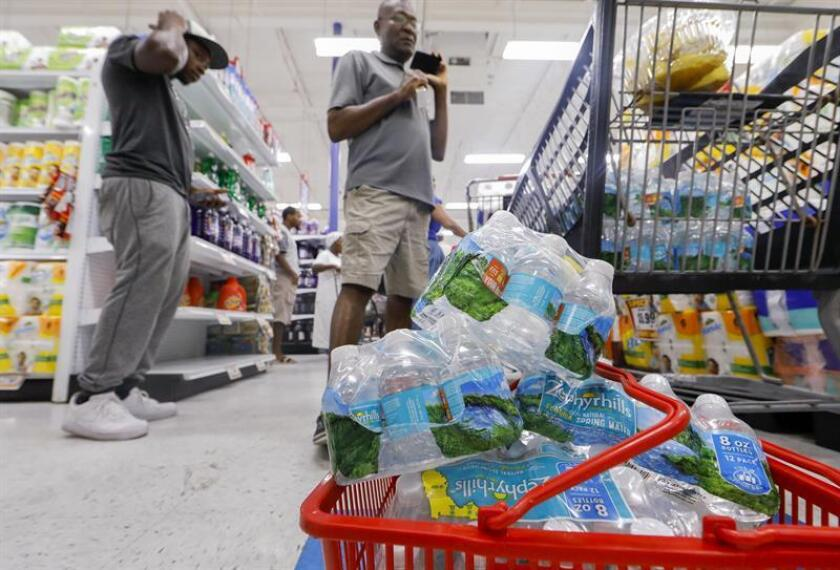 Dos hombres realizan compras en una tienda con estantes casi vacios en Miami. EFE/Archivo