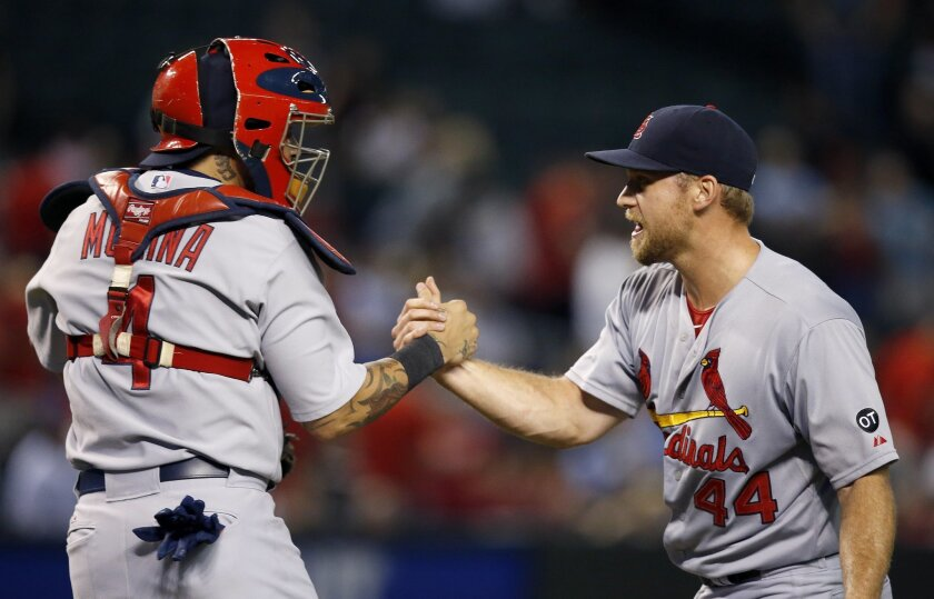 St. Louis Cardinals' Trevor Rosenthal (44) and Yadier Molina celebrate after the final out of a baseball game Wednesday, Aug. 27, 2015, in Phoenix. The Cardinals defeated the Diamondbacks 5-3. (AP Photo/Ross D. Franklin)