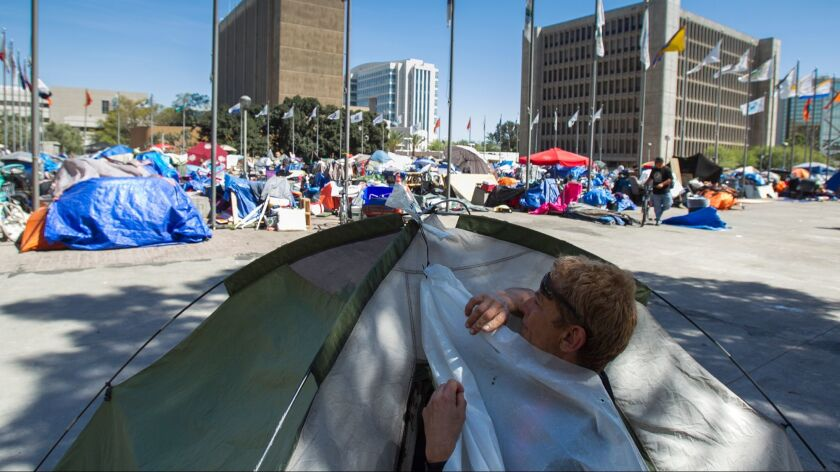Austin Flores sets up his tent at a homeless encampemnt at the Santa Ana Civic Center on Wednesday,