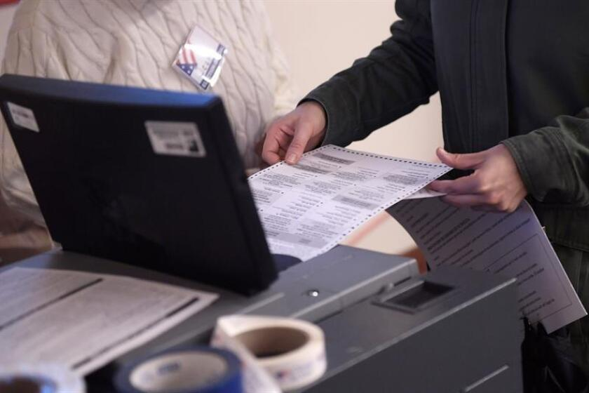 Una persona introduce su boleta de voto en una máquina de votos. EFE