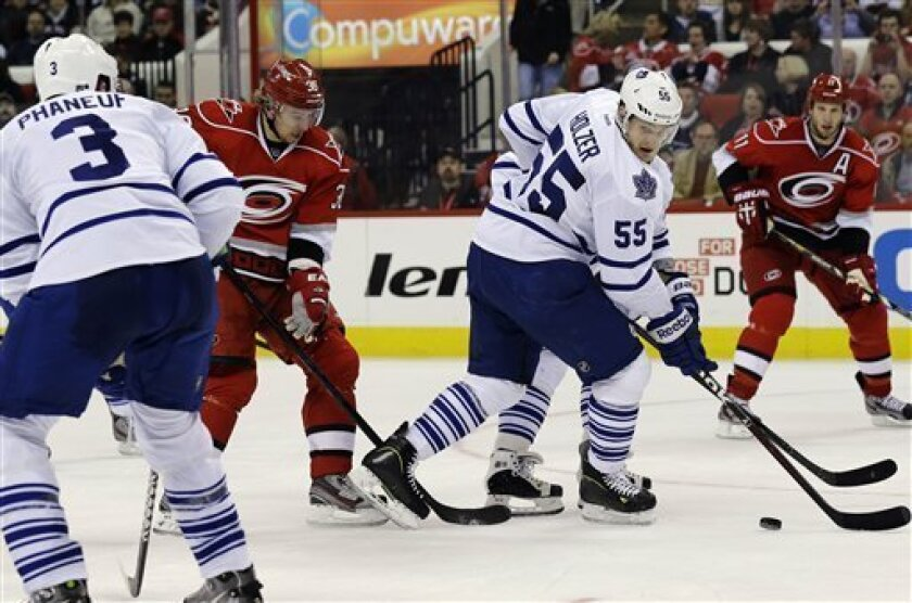Carolina Hurricanes' Jussi Jokinen (36), of Finland, shoots past Toronto Maple Leafs' Korbinian Holzer (55), of Germany, and Dion Phaneuf (3) during the second period of an NHL hockey game in Raleigh, N.C., Thursday, Feb. 14, 2013. Jokinen scored on the play. (AP Photo/Gerry Broome)