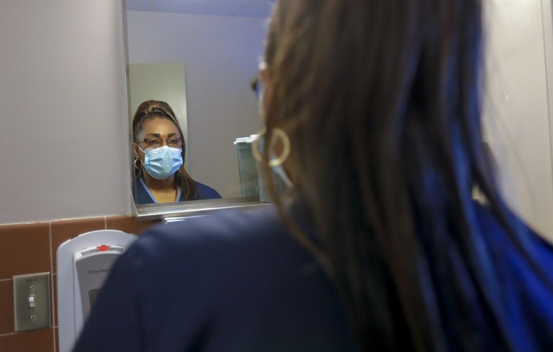 Connie Wright, empleada de intendencia del Centro Médico de San Diego, se pone una máscara durante su turno.