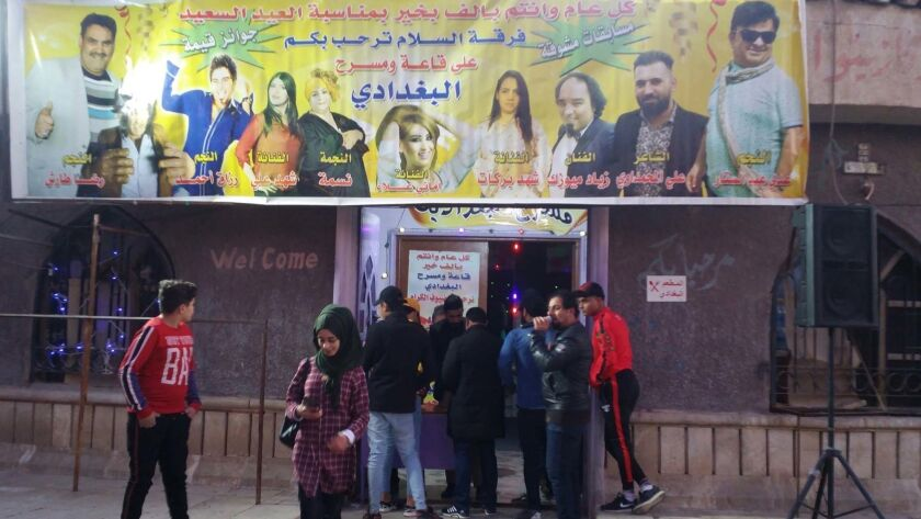 A comedian exhorts passers-by to attend a show. Baghdad is known for its theaters.