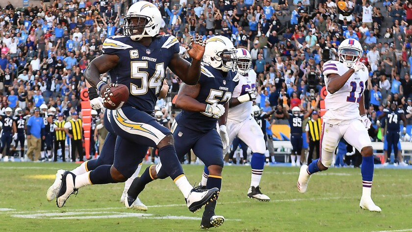 Chargers defensive end Melvin Ingram picks up a fumble by Bills quarterback Tyrod Taylor.