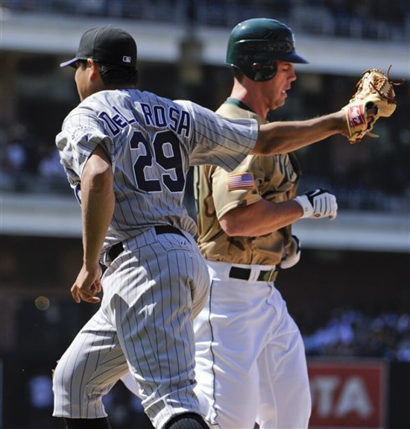 Colorado Rockies pitcher Jorge De La Rosa, left, tags out San Diego Padres' Clayton Richard, right, as he tries to beat a ground ball to first base during the fifth inning of a baseball game Sunday, Sept. 5, 2010 in San Diego. (AP Photo/Denis Poroy)