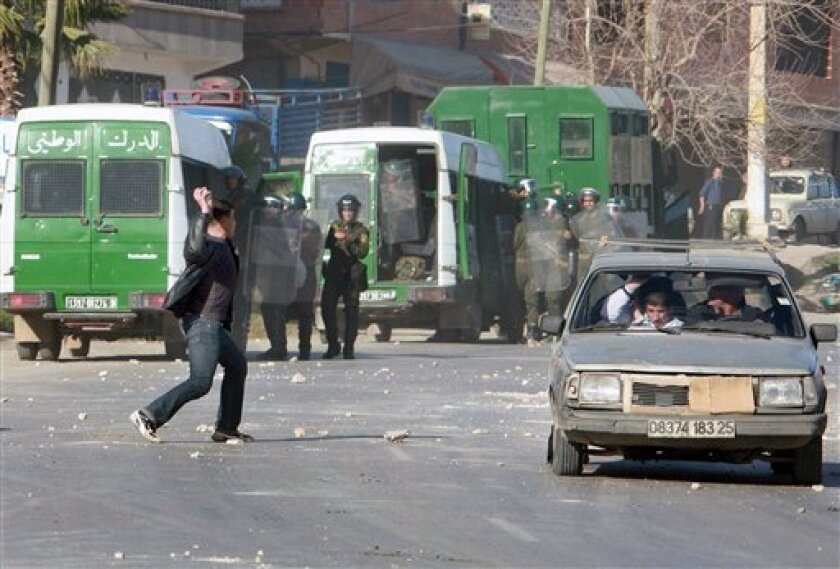 A demonstrator throws stones towards police forces in Constantine, eastern Algeria, Saturday Jan. 8, 2011 as people attempt to drive away from the area. Youths in the North African nation have been rioting for days following sudden price hikes for staples including sugar, flour and oil. (AP Photo)