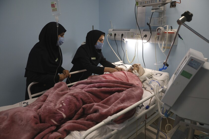 Covid-19 patient Marhamat Asadi which is in medically induced coma is tended by nurses Fatemeh Najmeh Sadeghi, left, and Fereshteh Babakhanlou at the COVID-19 ICU ward of Amir Al-Momenin hospital in the city of Qom, some 80 miles (125 kilometers) south of the capital Tehran, Iran, Wednesday, Sept. 15, 2021. (AP Photo/Vahid Salemi)