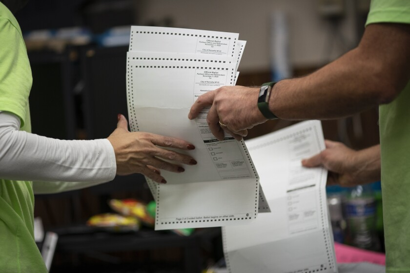 Poll workers sort early and absentee ballots on election day in Kenosha, Wis.