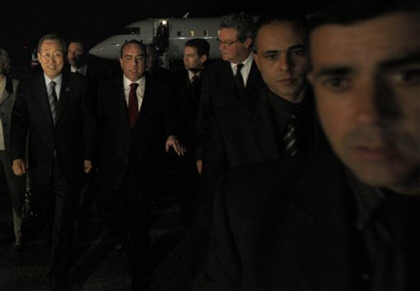 U.N. Secretary-General Ban Ki-moon, left, is welcomed by Cypriot Foreign Minister Marcos Kyprianou, second left, and with U.N Special Adviser for Cyprus, Alexander Downer, third left, after arriving in Larnaca airport to re-energize slow-moving talks to reunify the ethnically split island of Cyprus, Sunday, Jan. 31, 2010. Ban's first-ever visit to Cyprus is seen as a personal show of support for the open ended talks between the island's Greek Cypriot President Dimitris Christofias and breakaway Turkish Cypriot leader Mehmet Ali Talat. (AP Photo/Petros Karadjias)