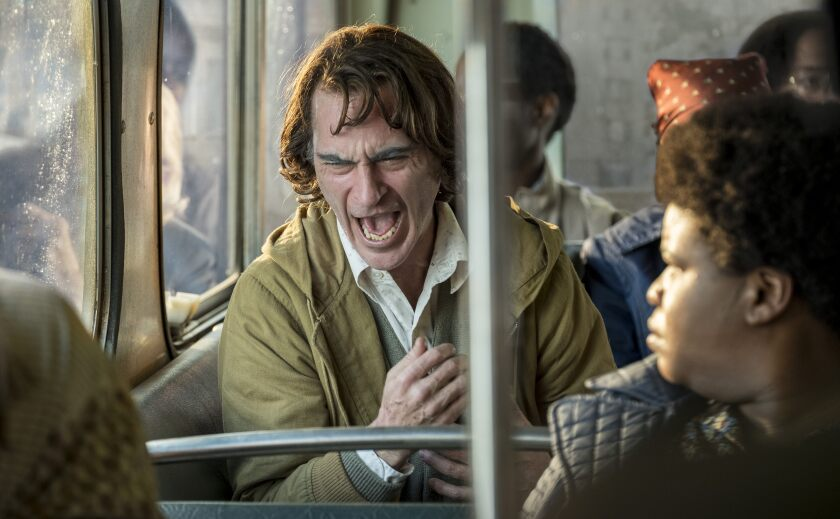 "Joaquin Phoenix as the ""Joker,"" mid-yell on a bus."