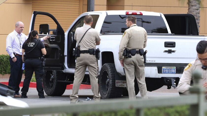 Las Vegas police surround a white pickup truck as they investigate after a pursuit related to the of