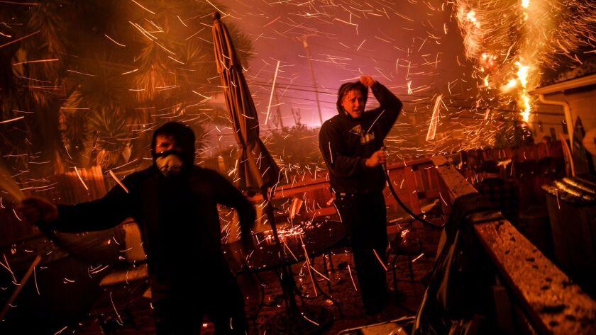 VENTURA, CALIF. -- TUESDAY, DECEMBER 5, 2017: John Bain and Brandon Baker take cover from the embers