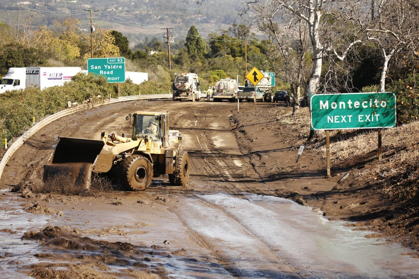 Crews work to clear debris from the closed 101 Freeway at Olive Mill Road in Montecito.