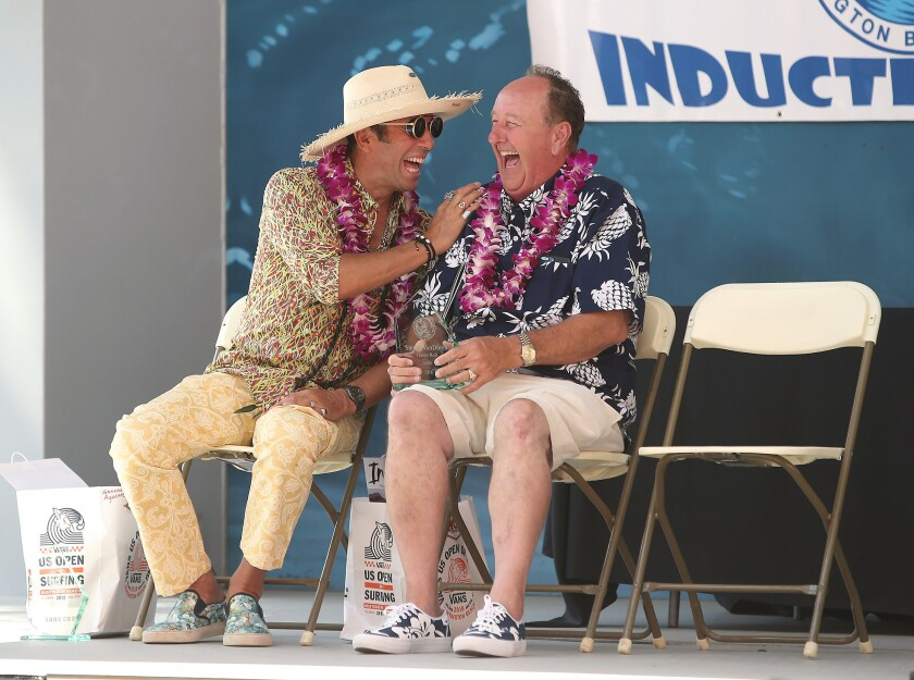 Honor Roll inductees Fernando Aguerre, left, and Steve Van Doren share a laugh during the Surfing Walk of Fame induction ceremony Thursday in front of Jack's Surfboards in Huntington Beach.