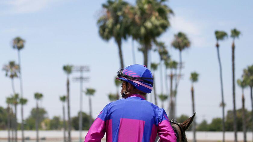 LOS ALAMITOS, CALIF. - JUNE 29, 2019. A jockey cools down his horse after a race at the Los Alamitos