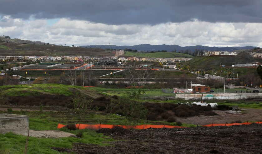Across the road from the Harmony Grove Village development, the denser central area is nearing completion, with the sewage treatment facility on the far right, and the green hills in the foreground of land that developers would like to expand into.