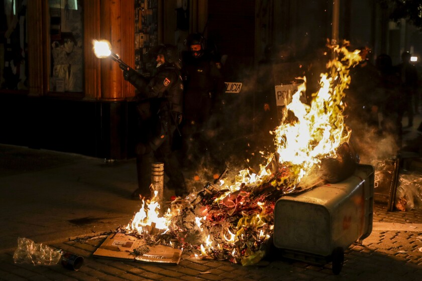 A police officer opens fire near a trash can set ablaze in Madrid