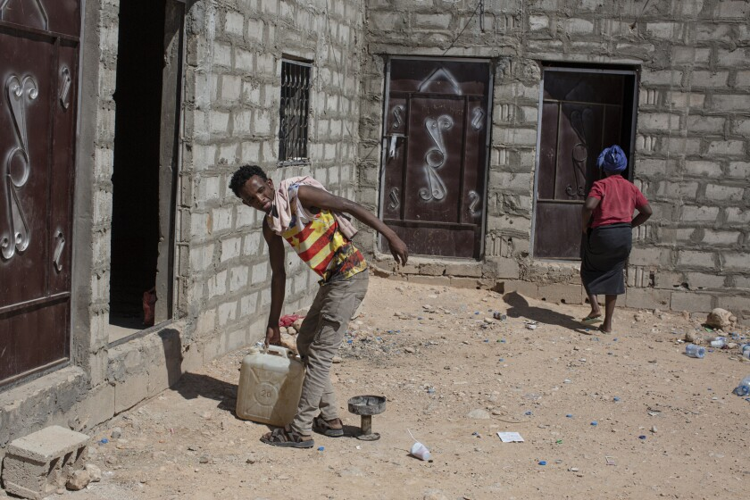 Tigra Hara Rayye, 23, an Ethiopian who came to Yemen a year ago, carries a jerry can of water in a compound for migrants.