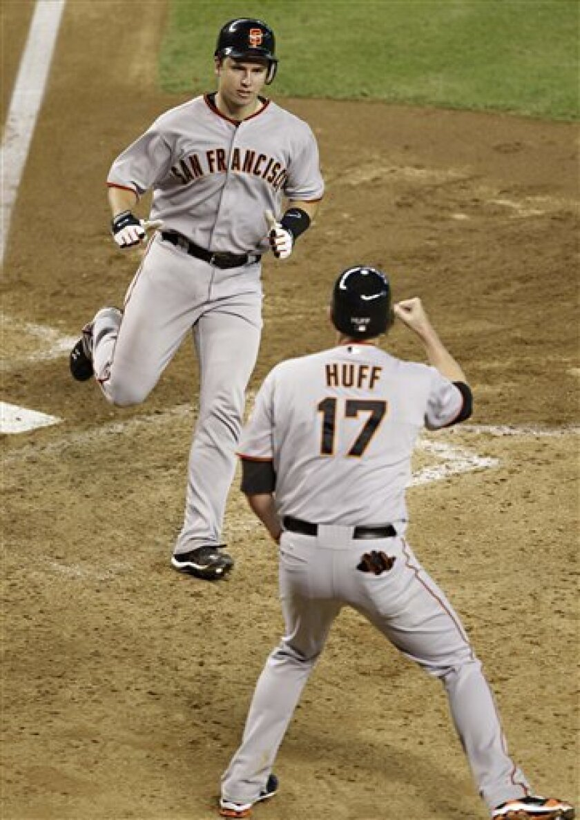 San Francisco Giants' Buster Posey and Aubrey Huff (17) score off a triple by teammate Nate Schierholtz during the 11th inning of a baseball game against the Arizona Diamondbacks Monday, Sept. 6, 2010, in Phoenix. (AP Photo/Matt York)