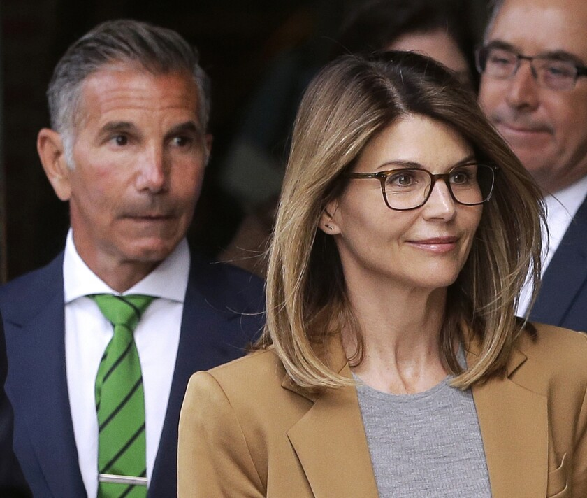 FILE - In this April 3, 2019, file photo, actress Lori Loughlin, front, and husband, clothing designer Mossimo Giannulli, left, leave federal court in Boston after facing charges in a nationwide college admissions bribery scandal. Lawyers for Loughlin and Giannulli filed court documents Friday, Nov. 1, saying the couple plans to plead not guilty to charges of conspiracy to commit federal program bribery. The couple also waived their right to appear at a Nov. 20 arraignment. (AP Photo/Steven Senne, File)
