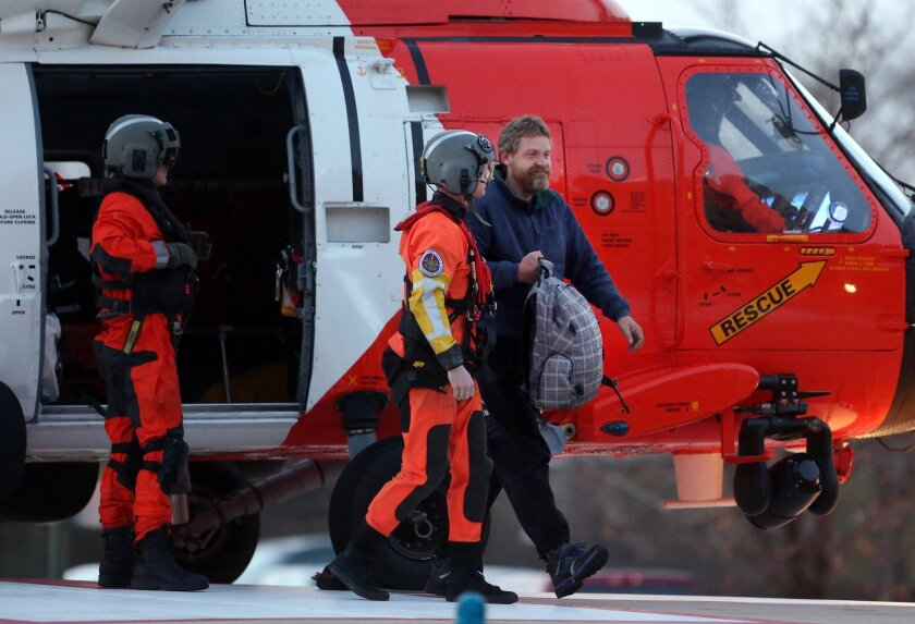 Louis Jordan, right, walks from the Coast Guard helicopter to the Sentara Norfolk General Hospital in Norfolk, Va., after being found off the North Carolina coast, Thursday, April 2, 2015. His family says he sailed out of a marina in Conway, South Carolina, on Jan. 23, and hadn't been heard from si