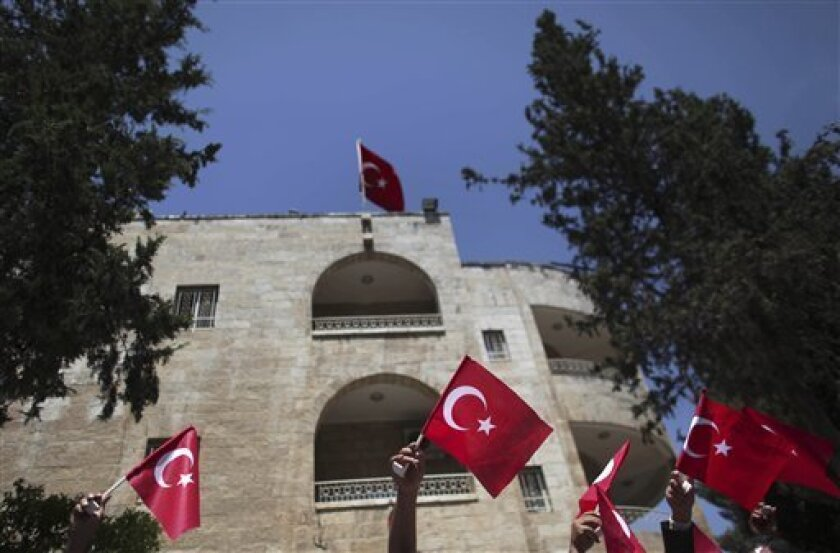 Palestinians wave Turkish flags in front of the Turkish consulate during a protest against the Israeli naval commando raid on a flotilla attempting to break the blockade on Gaza, in the east Jerusalem neighborhood of Sheikh Jarrah, Tuesday, June 1, 2010.  Some activists seized by Israeli authoritie