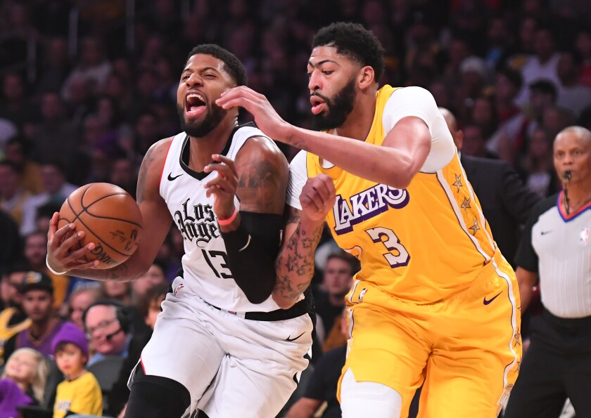 Clippers forward Paul George tries to drive past Lakers forward Anthony Davis during a game Dec. 25, 2019.