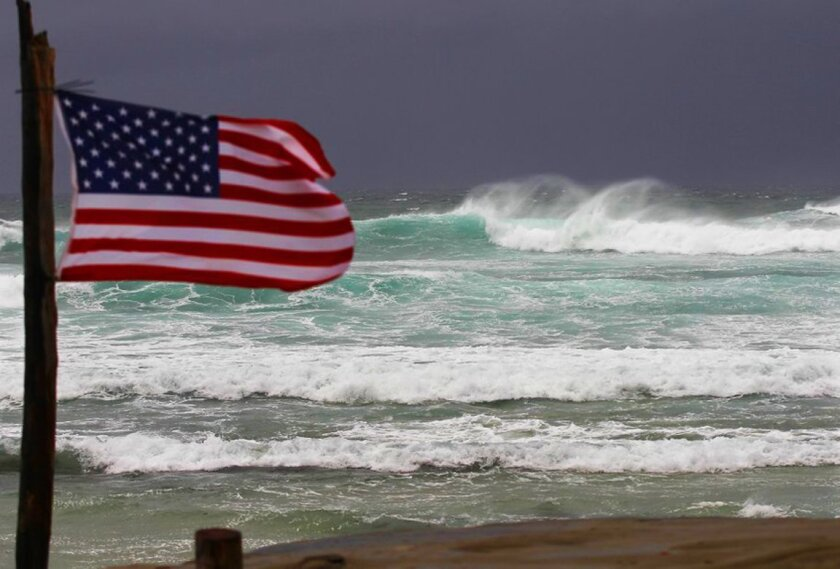 The wind whips a flag as waves break in La Jolla during an El Niño storm Wednesday, Jan. 6.