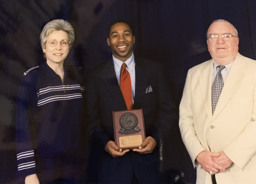 Martin Jarmond, center, holds an award he received from the National Assn. of Collegiate Directors of Athletics.