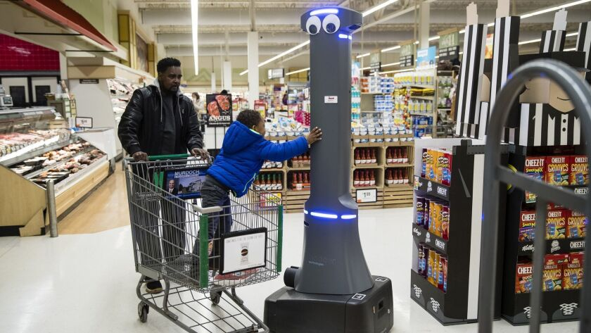 A child greets a robot named Marty as it monitors a Giant Food Stores grocery store in Harrisburg, Pa. The chain is putting the robots in all its stores.