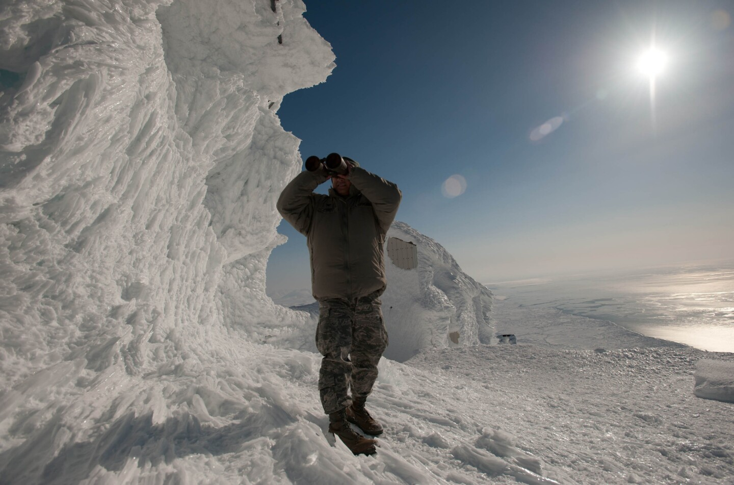 Air Force Col. Frank Flores uses binoculars to look across the Bering Strait toward Siberia from Tin City, a long-range radar station in remote Alaska.