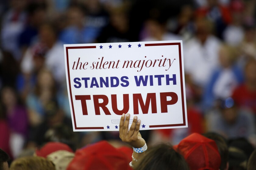 A Trump supporter holds a sign saying the