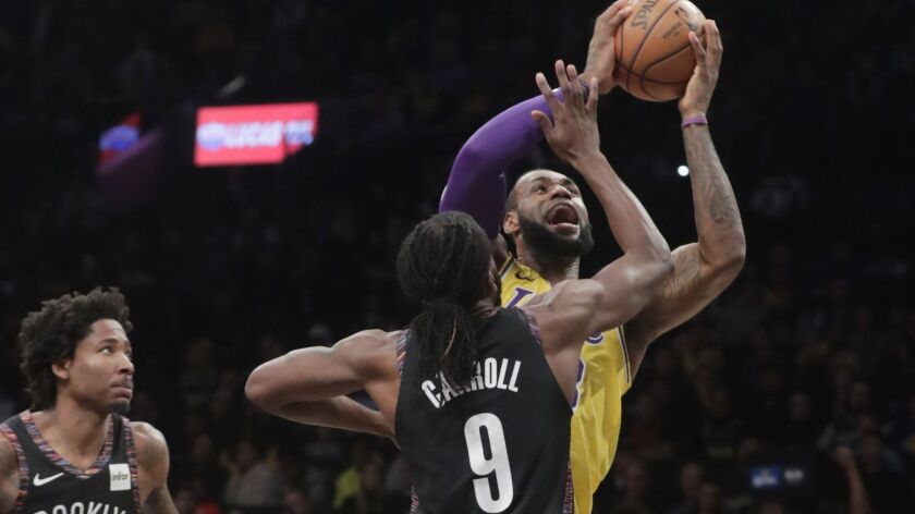 Lakers' LeBron James drives past Brooklyn Nets' DeMarre Carroll (9) during the first half on Tuesday in New York.