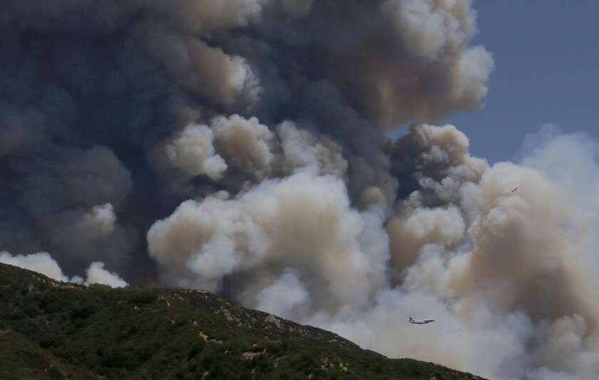 A firefighting jumbo jet is dwarfed by the smoke from the Apple fire in the hills above Beaumont.