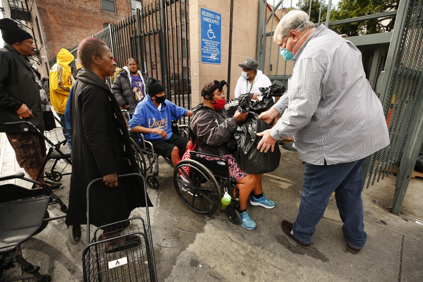 Herb Smith, right, president and chief executive of the Los Angeles Mission hands Juanita Glover a bag of food and hygiene products.
