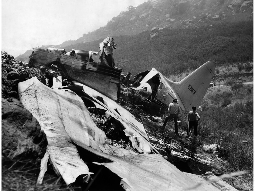 July 12, 1949: The battered fuselage and wing section of a C-46 Standard Airlines passenger plane li